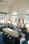 Island counter with barstools in converted loft with arched windows