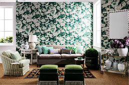 Green and white wallpaper with floral pattern and matching seating furniture in the living area