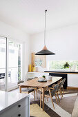 Pendant lamp above dining table with chairs in open living room
