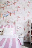 Bed with white and pink striped bed linen and wallpaper with bird motif in the girl's room