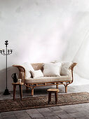 Candlestick next to rattan sofa with pillows and wooden stool