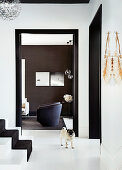 Diele mit weißer Boden und Treppenaufgang, Blick auf Sessel im Wohnzimmer