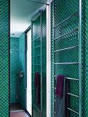 Handtuchtrockner und Spiegelwand in der Dusche mit Mosaikfliesen in Grüntönen