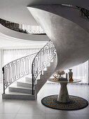 Elegant hall with spiral marble staircase and marble table