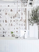 Botanical cards on the wall, olive trees and white desk