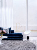 Blue upholstered sofa and coffee table in front of glass front