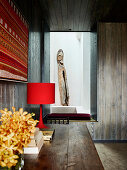 View over wooden table onto bench in alcove, wooden artwork in background