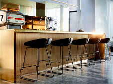 Kitchen island made of polished brass with bar stools in an elegant, open living room with marble tiles