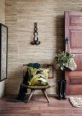Open wooden door to the hallway in shades of brown with gray wallpaper