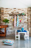 Children's table and chairs in front of brick wall in open living room