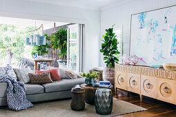 Sideboard, Zimmerpflanze, Couchtisch und Sofa vor geöffneter Terrassentür im Wohnzimmer