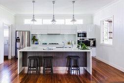 Offene Küche mit weißen Hochglanzfronten und Mittelblock
