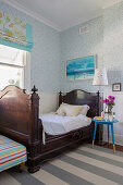 Antique french bed and blue bedside table in the youth room with white and blue wallpaper