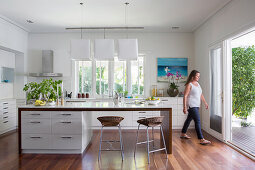 Kitchen island and bar stool in open kitchen with terrace access, woman in the background