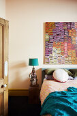 Antique table lamp on bedside table next to bed, modern art on wall in bedroom