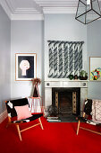 Two chairs on red carpet in front of fireplace in living room with light gray walls and stucco