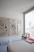 Large comic-style artworks in minimalist bedroom