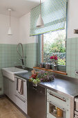 Green wall tiles and kitchen counter with stainless steel worktop below window in kitchen