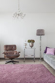 Classic armchair, serving trolley, standard lamp and grey sofa in living room