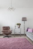 Klassikerstuhl, Servierwagen, Stehleuchte und graues Polstersofa im Wohnzimmer