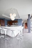 Verschiedene Barhocker um eine futuristische Kücheninsel