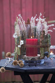 Candle lantern decorated with natural materials for winter on garden table