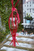Handmade suspended lantern made from candle in jar and red twigs