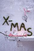 XMAS written on wall in moss as festive garden decoration