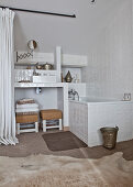 Bathtub in bathroom with white wall tiles and cowhide rug