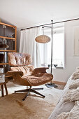 Classic leather armchair in front of standard lamp and window