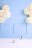 Two bunnies in the room with a light blue wall and huge paper flowers
