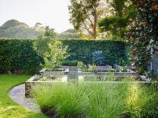 Hochbeete mit Holzeinfassung in elegant angelegtem Garten