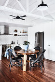 Round table and black chairs in dining area in front of fridge and white kitchen counter