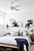 Double bed against ledge in wood panelling in white bedroom with ceiling fan