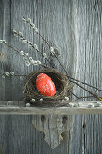 Hand-painted red Easter egg in willow nest and branches of pussy willow on wooden shelf