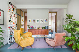 Retro armchairs in open-plan interior with pale blue floor