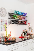Christmas decorations on kitchen base unit below shelves of multicoloured glass goblets