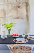 Set dining table below wicker lampshade on terrace