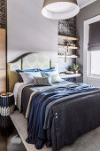 Bed with accessories in blue tones and clamped shelves in the bedroom