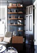 Bookshelf against dark wall next to open door in living room