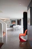 Orangefarbener Designerstuhl vor der Treppe im offenen Wohnraum