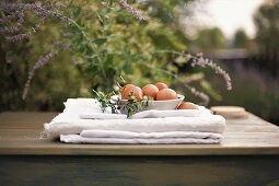 Bowl of eggs on stacked, folded cloths on table