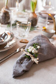 Sprig of berries and napkin tied with string on set dining table