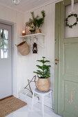 Green wooden door in festively decorated hallway