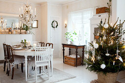 Festively decorated dining table and decorated Christmas tree in Scandinavian dining room