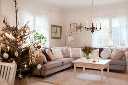Decorated Christmas tree next to grey corner sofa in living room