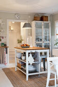 Island counter with open-fronted shelves and glass-fronted cabinet in rustic kitchen