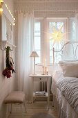 Bedside table and bed in front of window in bedroom decorated for Christmas
