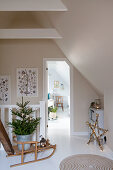 Fir tree on sledge in attic stairwell