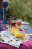 Pears and tea on set table in garden